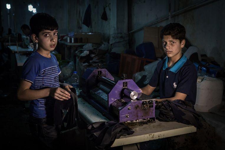 Morad Bozan (links), 11 jaar en Hassan Mahfouz, 14 jaar, beiden uit Aleppo, maken slippers. Beeld Cigdem Yuksel