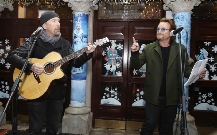 The Edge (links) en Bono tijdens het optreden voor daklozen op Grafton Street in Dublin.