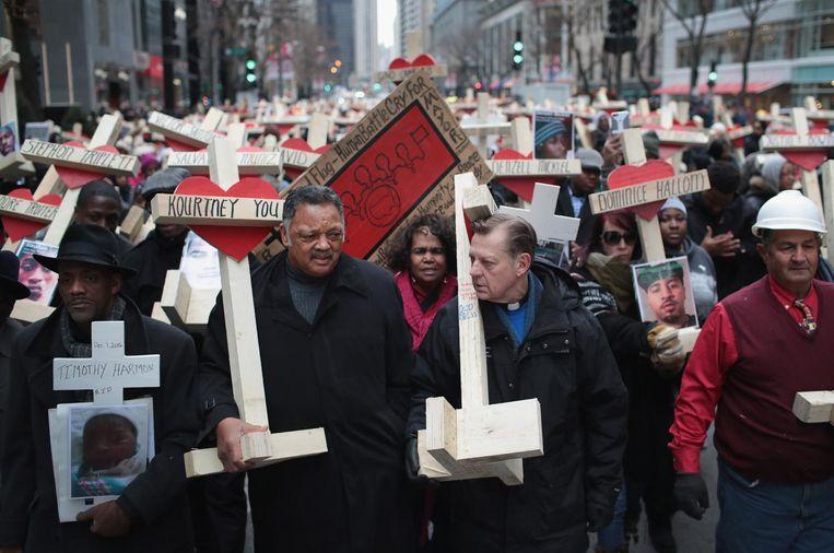 Inwoners van Chicago doen mee aan een mars waarbij ze kruizen dragen voor vermoorde stadsgenoten. Beeld afp