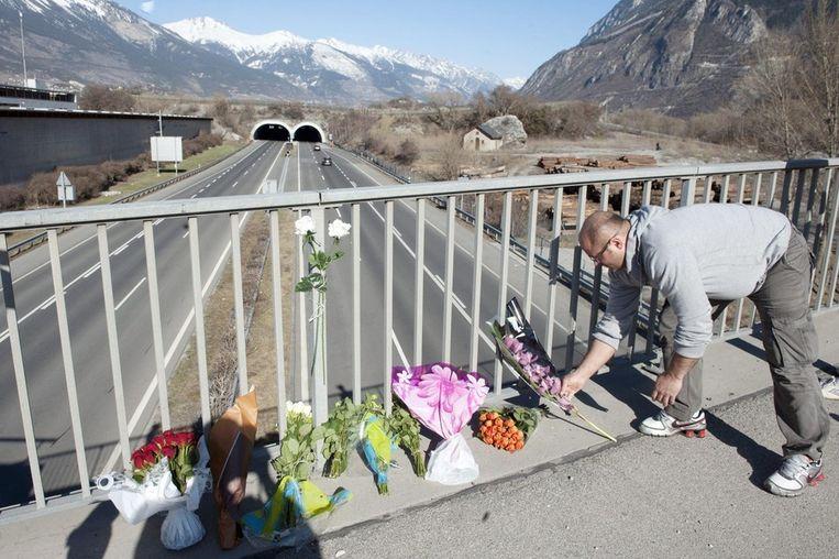 Mensen leggen bloemen neer nabij de ingang van de tunnel aan de snelweg A9.