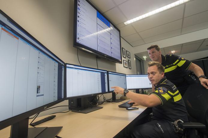 Een kijkje achter de schermen bij het webcare-team van de politie, dat vanaf donderdag voor heel Twente actief is. Joost van Goor (vooraan)  en Sjoerd Obbink bij de social media schermen.