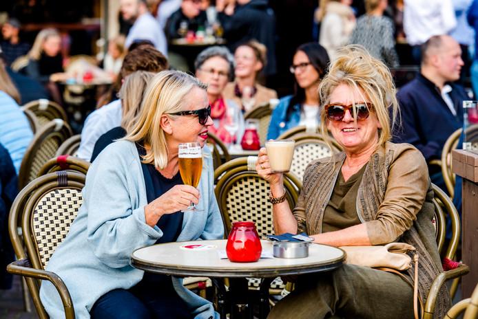 Mensen genieten van het mooie weer op het terras van Van Zanten in Rotterdam.