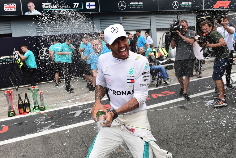 Lewis Hamilton viert zijn overwinning met champagne in Monza in 2018.