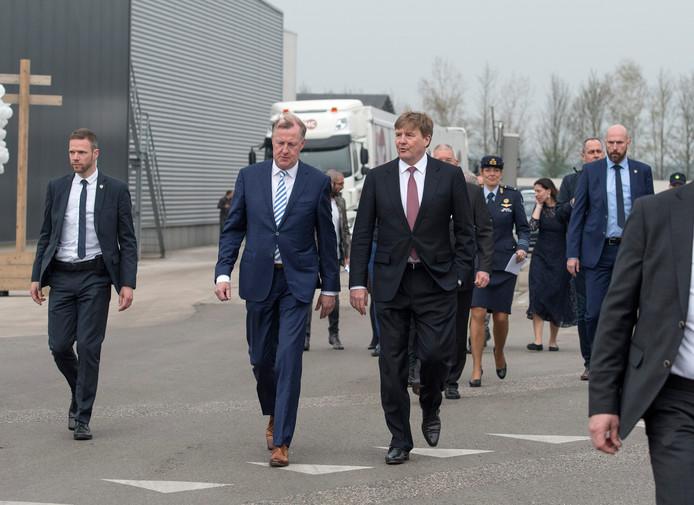 Koning Willem Alexander koos ervoor om lopend naar de uitgang van het bedrijventerrein te gaan. Directeur Tom van Wijk begeleidt hem. Net als zijn grote gevolg.