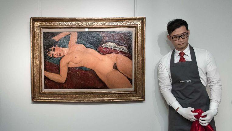 Een medewerker van Christies naast het doek van Amedeo Modigliani. Beeld anp