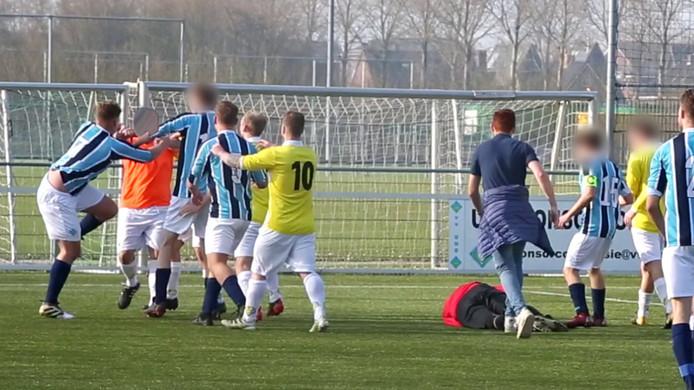 De grensrechter (in het oranje) net nadat hij de doelman (in het rood) bewusteloos heeft geslagen.