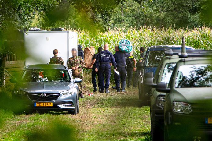 Politiemensen voeren spullen af bij het bosperceel waar onderzoek wordt gedaan naar eenwapenvondst.