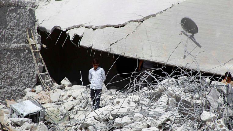 Een man in Idlib, Syrië, tussen de puinhopen van een gebouw dat door Amerikaanse bommen is geraakt. Beeld null