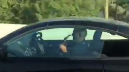 Automobilist speelt gitaar  terwijl hij wagen bestuurt op snelweg