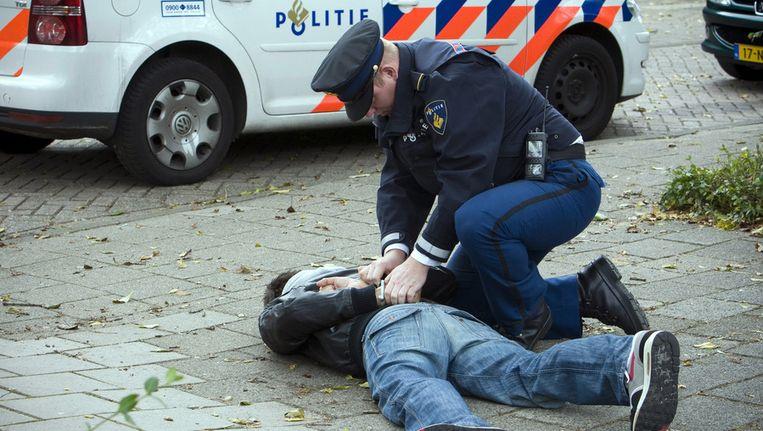 Een verdachte wordt in de boeien geslagen. Beeld ANP