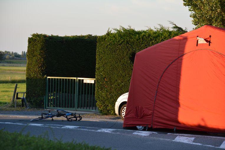 De verhakkelde fiets en de tent over het slachtoffer op de plaats van het ongeval.