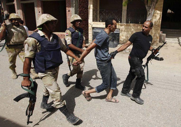 Eén van de 185 verdachten van de aanval op het politiebureau wordt gearresteerd. Beeld reuters