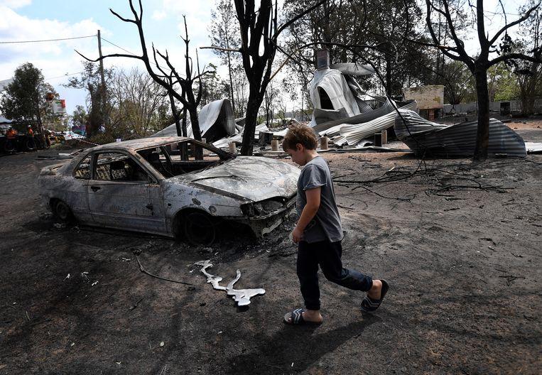 De 8-jarige Jarrod McInnes wandelt naast het huis dat zijn familie wilde kopen, maar volledig vernietigd werd door de bosbrand.
