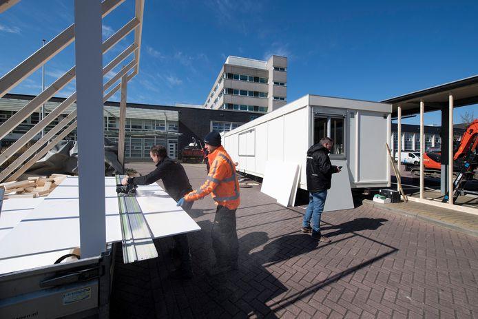 Bouwbedrijf De Vree en Sliepen plaatst noodunits voor huisartsen bij Ziekenhuis Rivierenland: doel is daar mogelijke coronapatiënten te zien.