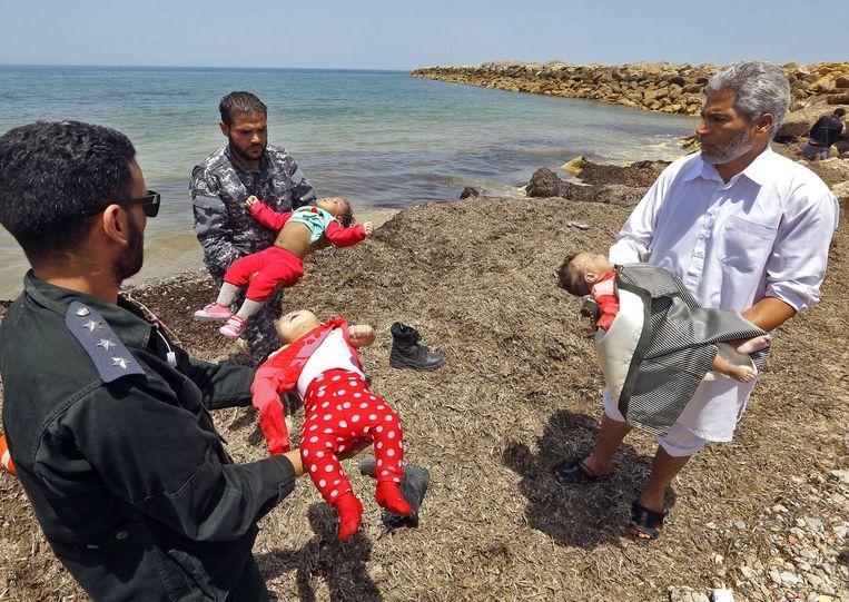 De dode lichamen van drie kinderen worden het land op gedragen.  Beeld AFP