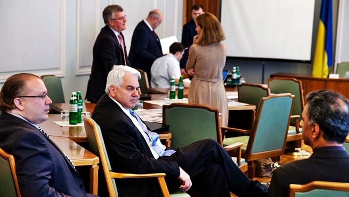 Op de achtergrond praat de Nederlandse plaatsvervangend ambassadeur Gerrie Willems (op de rug gezien) met de ambassadeur van Groot-Brittannië (links).