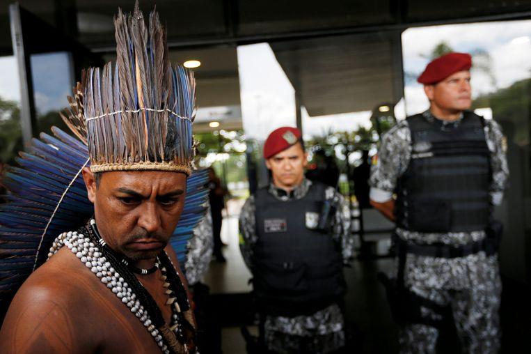 Een inheemse man wil een brief bezorgen aan de Braziliaanse president Bolsonaro bij een regeringsgebouw in Brasilia, 6december 2018.  Beeld Reuters