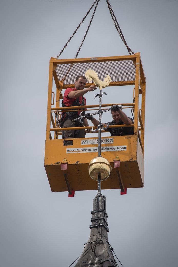 Monteurs van Royal Eijsbouts monteren de opnieuw vergulde haan op de toren van de Nicolaaskerk in Heino. Ook de bol aan de onderzijde van het kruis blinkt als vanouds.