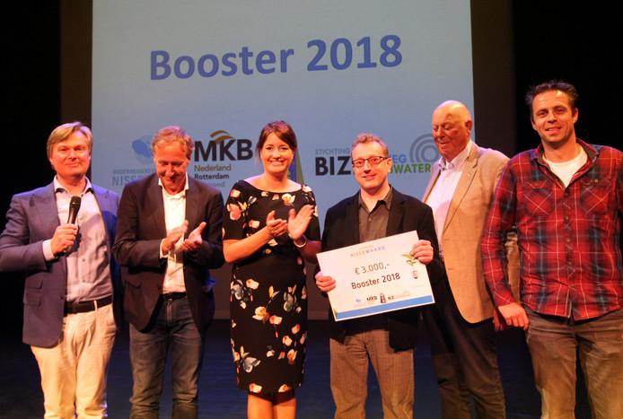 Winnaar Yuri Versteeg krijgt in theater De Stoep een cheque uit handen van oud-wethouder Christel Mourik.