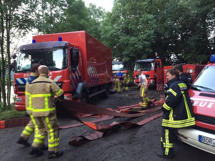 Brandweerkorpsen uit de Achterhoek helpen hun Duitse collega's met het wegpompen van het water.