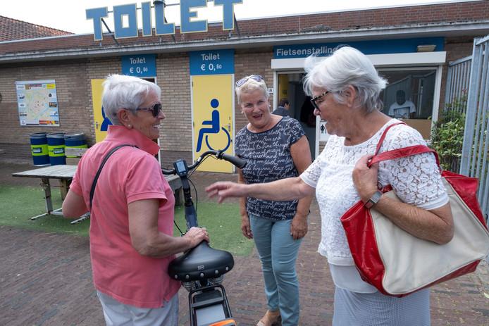 Vrijwilligster Jos Salhuteru (midden) helpt Will Wasser (links) en Diny de Hair uit Helmond, die hun fietsen komen parkeren in de fietsenstalling aan het Zusterplein in Middelburg. Bezoekers kunnen ook folders en een plattegrond van Middelburg meenemen.