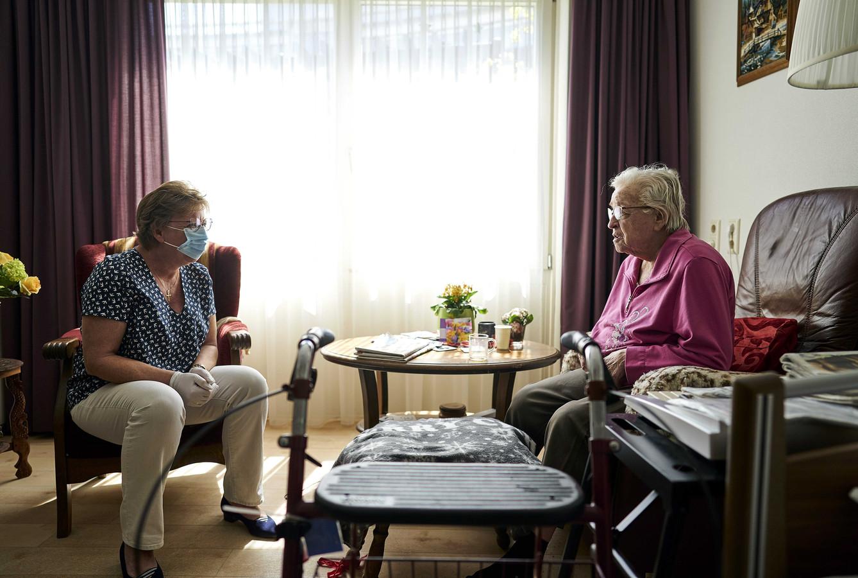 Een bewoonster van een verpleeghuis krijg bezoek van iemand met een mondkapje. Ouderenbond ANBO vindt dat het gebruik van mondkapjes in verpleeghuizen verplicht moet worden gesteld.