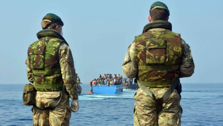 Soldaten staan klaar om bootvluchtelingen op te vangen.