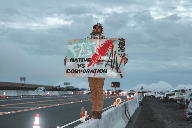 Een kia'i, een beschermer, maakt met zijn bord bij de Mauna Kea duidelijk waar het conflict om draait. Beeld Cody Fay