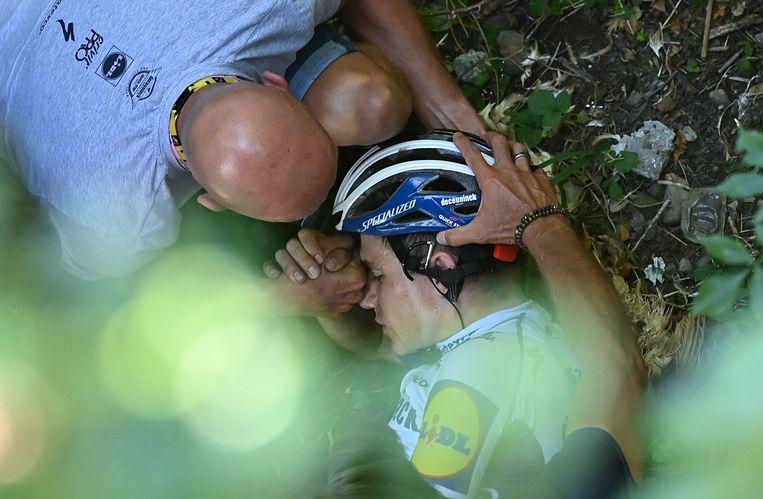 Remco Evenepoel, de ogen gesloten, na zijn val. Beeld AFP