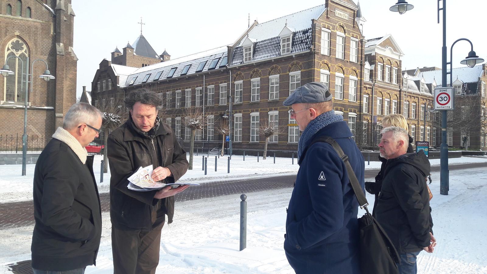 Voorzitter Bernard Vissers (tweede van links) van heemkundekring Vechele geeft een historische rondleiding door Veghel.