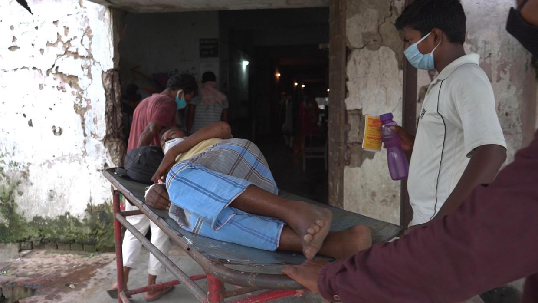 Een patiënt wordt het ziekenhuis binnengereden in het academische ziekenhuis DMCH in Darbhanga in Bihar, India.