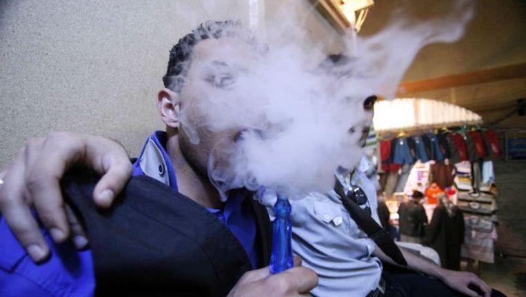 Twee moderne jongeren die zichzelf emo noemen, roken, heel traditioneel, een waterpijp. Beeld AP