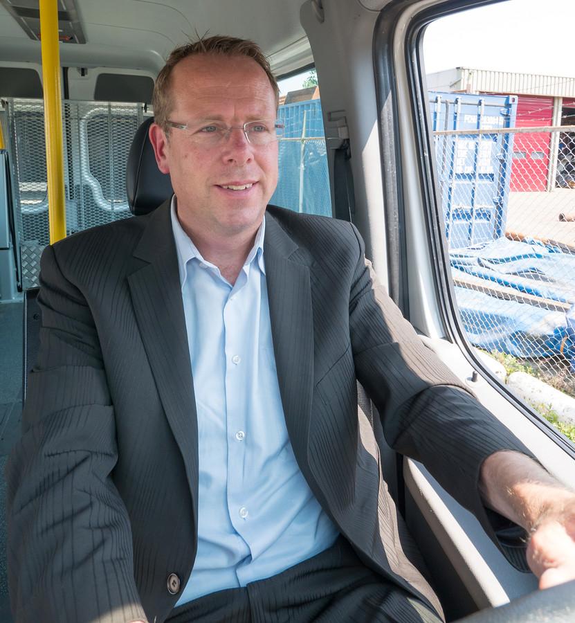 Nieuwkoopse taxi-ondernemer John van der Laan achter het stuur van één van zijn busjes. FOTO MARTIN SHARROTT