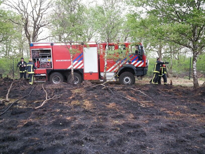 De Brandweer van Rheden blust de smeulende restanten.