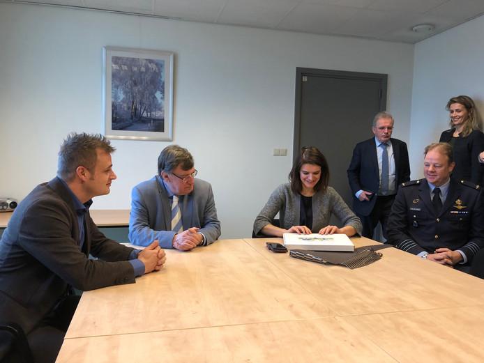 Staatssecretaris Barbara Visser (Defensie) pakt het cadeautje van de gemeente Uden uit. wethouder Gijs van Heeswijk, burgemeester Henk Hellegers en commandant Rob van den Heuvel van de vliegbasis Volkel kijken toe.
