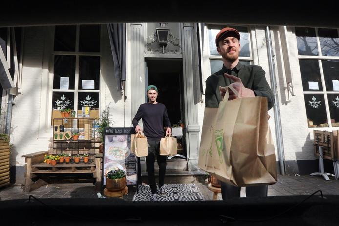 Roy Mossink (r) en Rein Baartmans van Barista Café brengen de te bezorgen koffie en taart naar de auto.