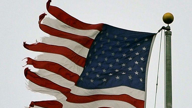 Een Amerikaanse vlag in Washington is gescheurd nadat orkaan Irene in augustus over de stad trok. © afp Beeld