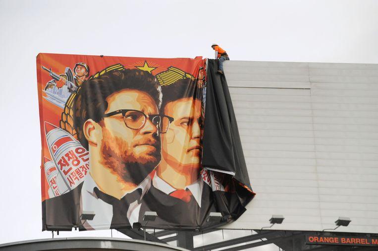 Een banner van de film The Interview in Hollywood, California, wordt verwijderd nadat Sony bekend heeft gemaakt dat de film niet zal verschijnen. Beeld afp