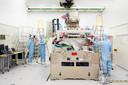 Werknemers van ASML werken in een stofvrije ruimte aan een chipmachine.