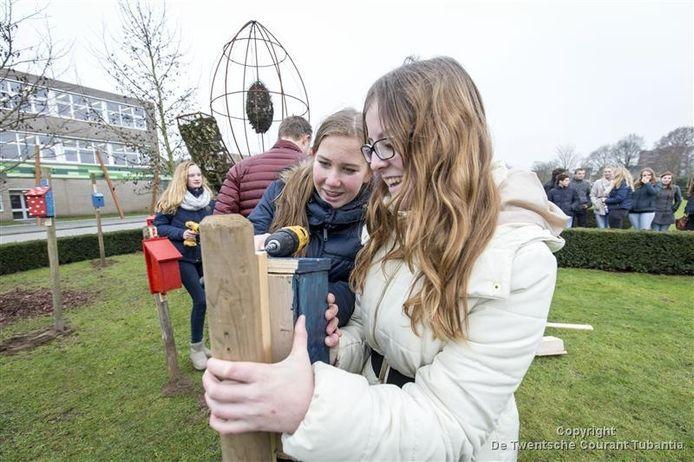 De AOC-leerlingen Jolijn Remmink (links) en Bridget Reinders plaatsen een van de vogelhuisjes bij hun school.