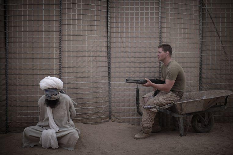 Een Amerikaanse marinier houdt een Afghaanse gevangene onder vuur op de Amerikaanse marinebasis in Marjah.   Beeld AFP