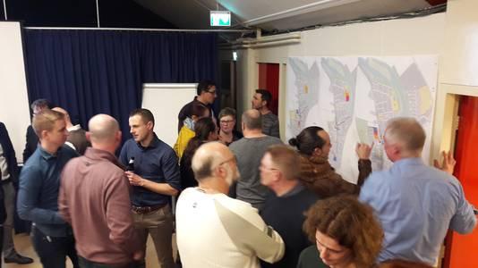 Disussie na afloop presentatie toekomstplannen voor Hoek waarvan de kaarten aan de wand zijn opgehangen.