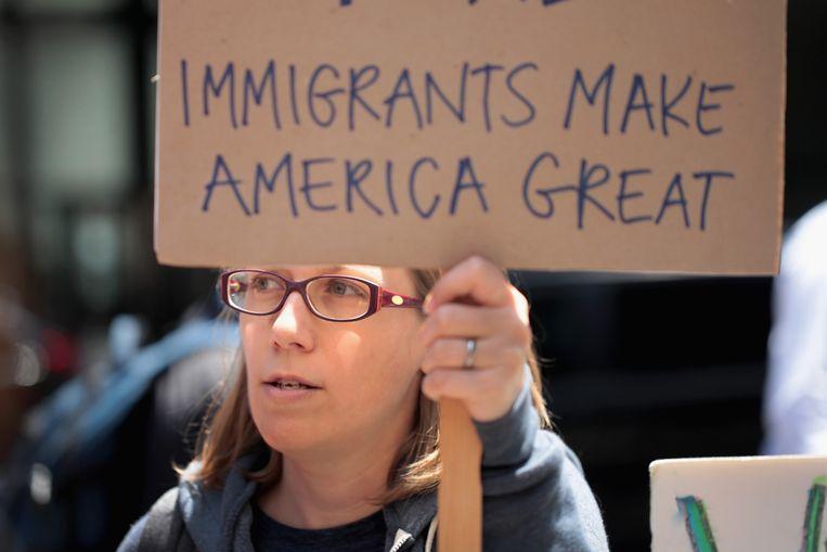 In Chicago houdt een demonstrant een bord omhoog met de tekst 'Immigranten Maken Amerika Groot', een slimme twist op Trumps verkiezingsslogan.