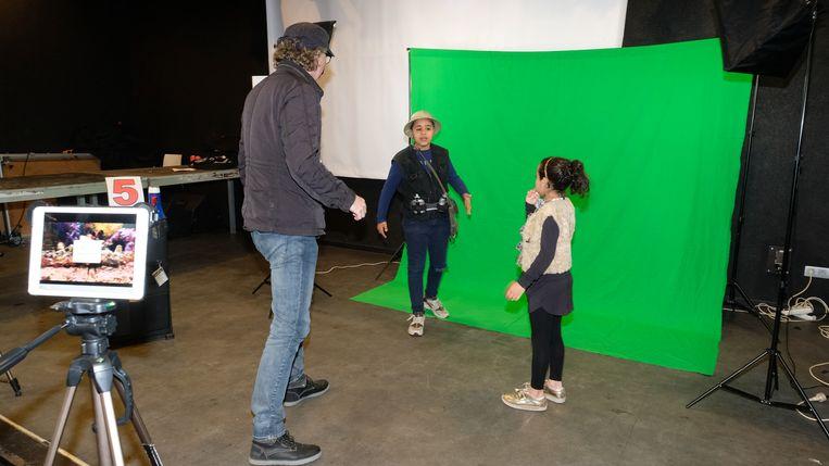 De jonge acteurs Janin en Noor voor het groene doek: daarop wordt het door de kinderen gekozen decorstuk geprojecteerd.