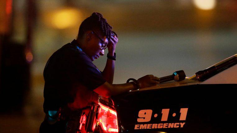 Een agente in Dallas neemt vrijdagochten even een momentje om zichzelf bij elkaar te rapen tijdens het bewaken van een kruispunt. Beeld ap