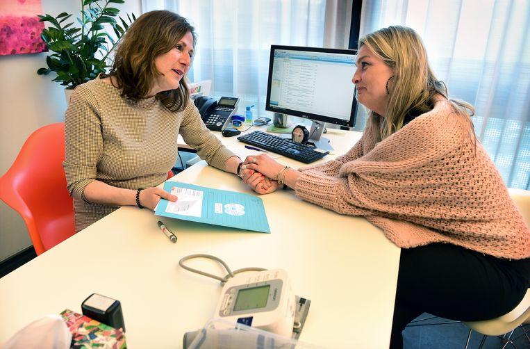 Meggy Drost (rechts) overhandigt huisarts Ingrid de Voogd informatie over meningokokken B. Haar dochtertje Sammie overleed aan de gevolgen van een besmetting met deze bacterie. Beeld Marcel van den Bergh
