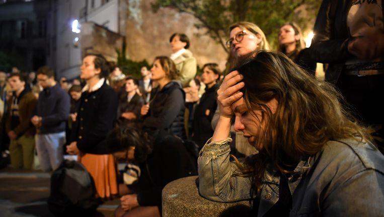 Aangeslagen knielen omstanders neer op de stoep in de buurt van de Notre-Dame. Beeld ANP