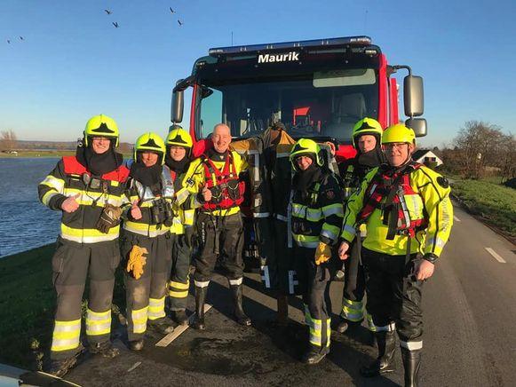 De brandweerlieden, samen met de opgeviste vogelverschrikker.