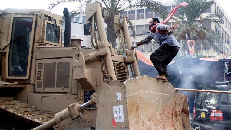 Een aanhanger van Morsi's Moslim Broederschap op een van bulldozers die de tentenkampen met de grond gelijk maakte. Beeld epa