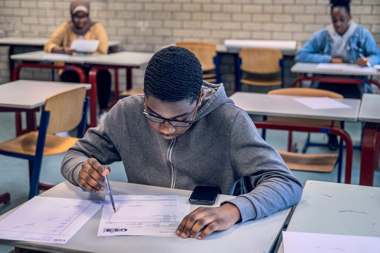 Patrick (15) is geslaagd en tekent zijn cijferlijst op de Openbare Schoolgemeenschap Bijlmer in Amsterdam.